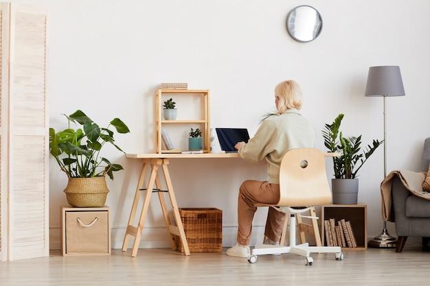 Вид сзади женщины, сидящей за столом и работающей на ноутбуке в комнате дома