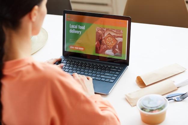 Вид сзади женщины, сидящей за столом перед ноутбуком и заказывающей еду онлайн