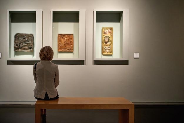 Вид сзади женщины, сидящей в художественной галерее перед красочными картинами