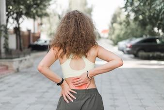 Rear view of woman standing on street having backache