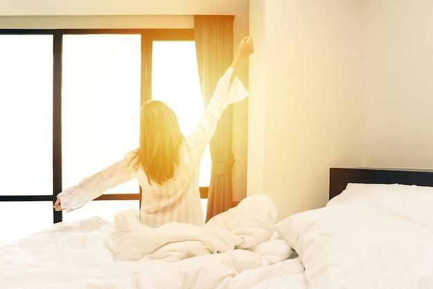Вид сзади женщины, растянувшейся в постели после пробуждения утром с солнечным светом