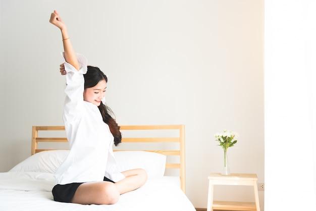 Вид сзади женщины, растянувшейся утром после пробуждения на кровати возле окна