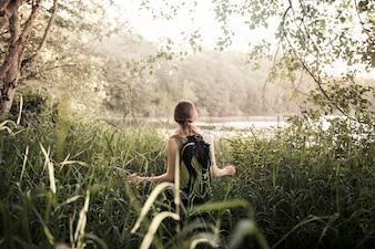 Rear view of woman walking in green grass near the lake
