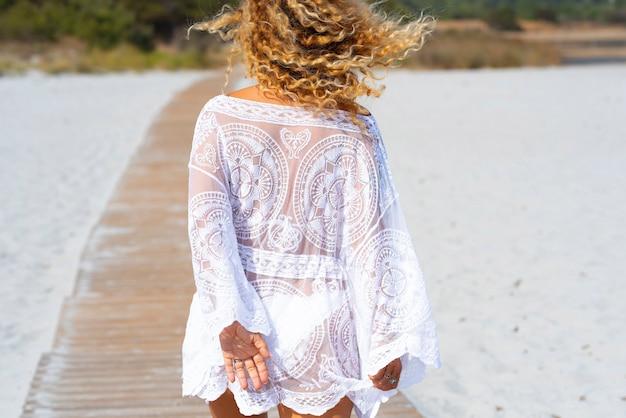 ビーチで砂の上を歩く女性の背面図。ビーチで砂に囲まれた歩道を歩いている白いドレスを着た女性観光客の背中。ビーチで休日を楽しむ女性旅行者