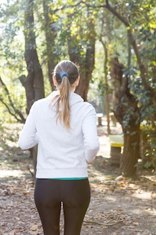 Rear view of woman with a ponytail running in the park