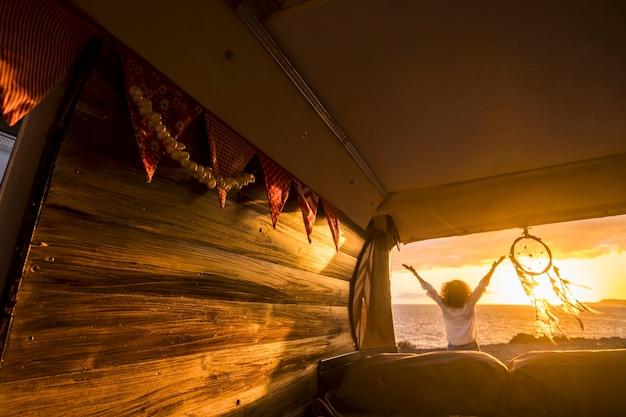 キャンピングカーからぶら下がっているドリームキャッチャーの横にある日没時の美しい海の景色を眺めながら腕を伸ばした女性の背面図。ドリームキャッチャーによってビーチで彼女の休暇を楽しんでいる巻き毛の女性