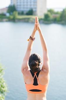 Вид сзади женщины с браслетом из бус, стоящей на берегу озера и ощущающей гармонию с йогой