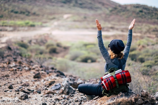 Вид сзади женщины со светлыми вьющимися волосами, занимающейся йогой и медитирующей во время путешествия, треккинга, пешего туризма, приключенческой деятельности - наслаждения и ощущения природы - здоровый образ жизни людей