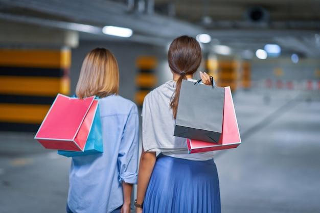 Вид сзади женщин с хозяйственными сумками на подземной автостоянке