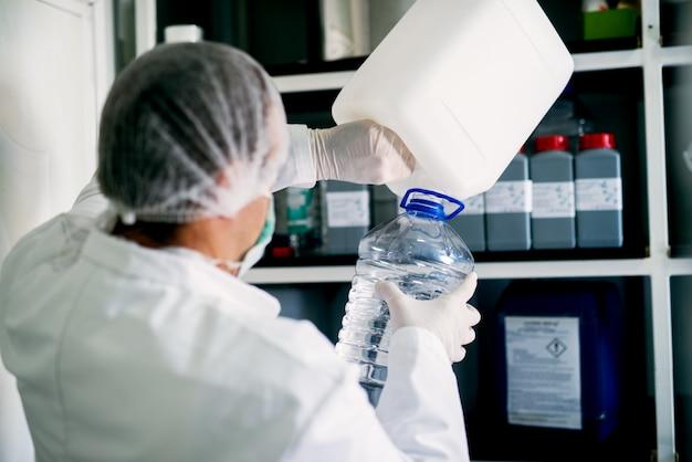 実験室の地下室で1つのボトルから別のボトルに透明な液体を均一に注ぐ作業員の背面図。