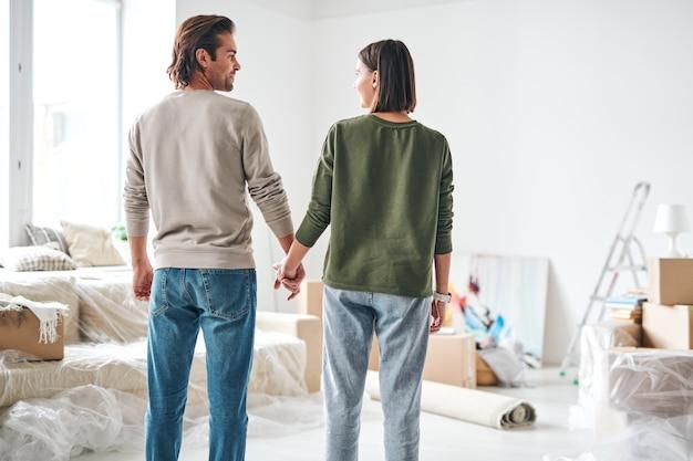 リビングルームに立っている間手で保持しているカジュアルウェアで若い愛情のこもった夫と妻の背面図