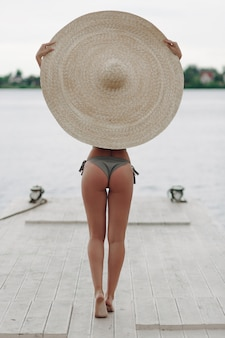 Rear view of Young afro woman back sexy swimsuit and big summer sombrero hat