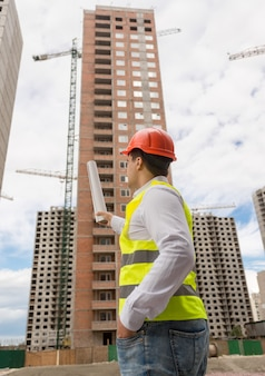 Вид сзади молодого архитектора, указывая чертежами на строящееся здание