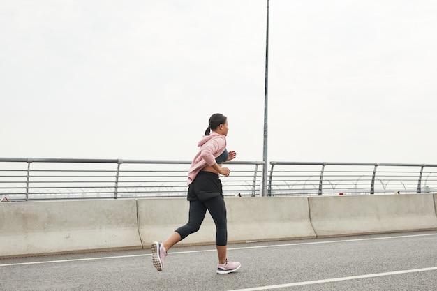 新鮮な空気の道に沿って朝走っている若いアスリートの背面図