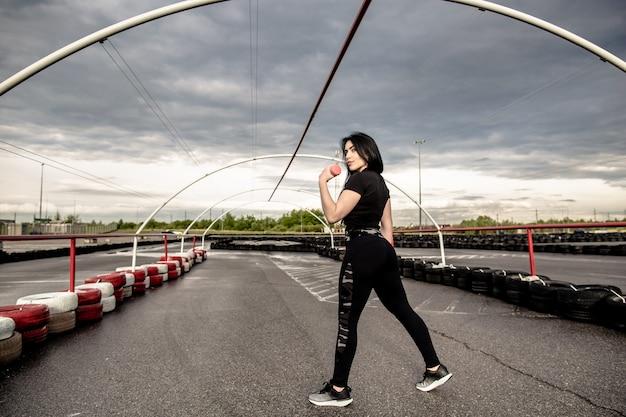 Covid-19の隔離後、屋外の遊び場でダンベル運動を行う運動少女の背面図。ヘルスケア、スポーツコンセプト