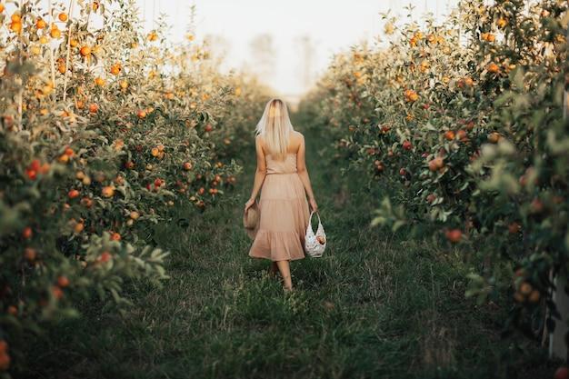 麦わら帽子、庭でポーズをとって柔らかいドレスを着ているブロンドの髪を持つ若い美しいファッショナブルな女性の背面図。