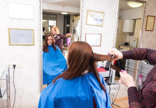 背景の大きな鏡でぼやけた反射とサロンで女性ブルネットクライアントの長い髪にフラットアイロンを使用して若いブロンドのスタイリストの背面図
