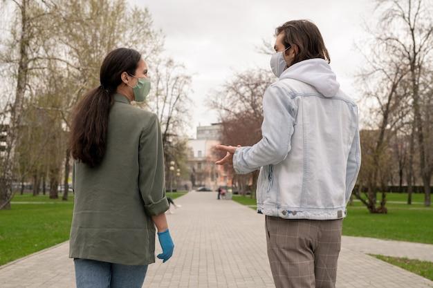 공공 공원에서 도로를 따라 이동하면서 이야기하는 마스크와 casualwear에서 젊은 현대 부부의 후면보기