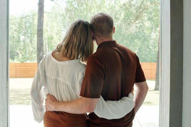 Вид сзади молодой пары, обнимающей друг друга, мечтающей о будущем в новом доме