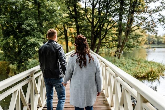 Вид сзади молодой пары, держась за руки во время прогулки по мосту
