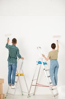 Вид сзади молодой пары в повседневной одежде, стоящей на стремянках и раскрашивающих стену малярным валиком, делая интерьер своей мечты в новой квартире