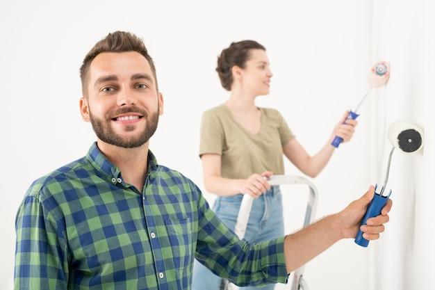 Вид сзади молодой пары в повседневной одежде, стоящей на стремянках и раскрашивающей стену малярным валиком, делая интерьер своей мечты в новой квартире