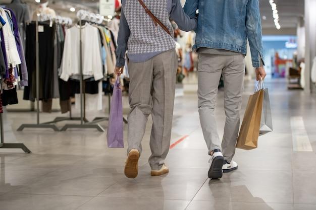 衣料品店を歩いているカジュアルウェアの若いカップルの背面図