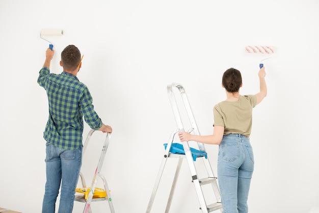 Вид сзади молодой пары, окрашивающей стену в белый цвет с помощью малярного валика при ремонте своей старой комнаты