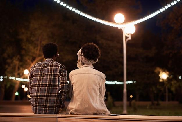公園で夜のロマンチックなデート中にベンチに座っている若いカップルの背面図