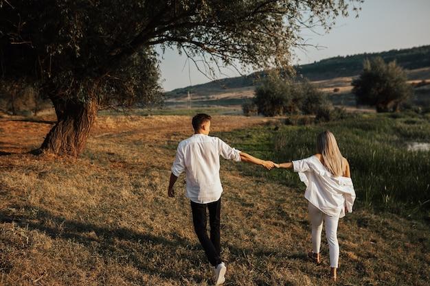 공원에서 산책하는 젊은 부부의 후면 볼 수 있습니다. 부부는 초원 산책을 즐기고 있습니다. 그들은 손을 잡고 있습니다.