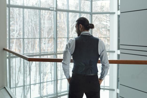 大企業のカンター内の手すりのそばに立っている間、ポケットに手を入れて正装で若いエレガントなビジネスマンの背面図