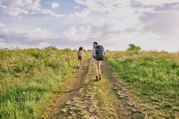 Вид сзади молодой женщины-путешественницы с рюкзаком, бегущей по проселочной дороге, в то время как ее муж с рюкзаком стоит позади и смотрит в сторону