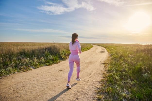 Вид сзади молодой подтянутой брюнетки в розовой спортивной одежде, бегущей по степной дороге на природе с красивым закатом