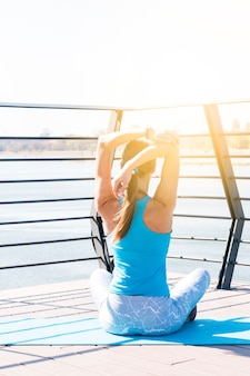 Rear view of young fitness woman stretching her hand sitting on bridge in morning sunlight