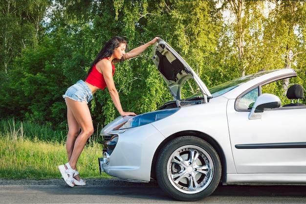 Молодая девушка в синих коротких джинсовых шортах ремонтирует машину, вид сзади. задницы в шортах возле серебристой машины с открытым капотом. проблемы с машиной в дороге. брюнетка ремонтирует двигатель.