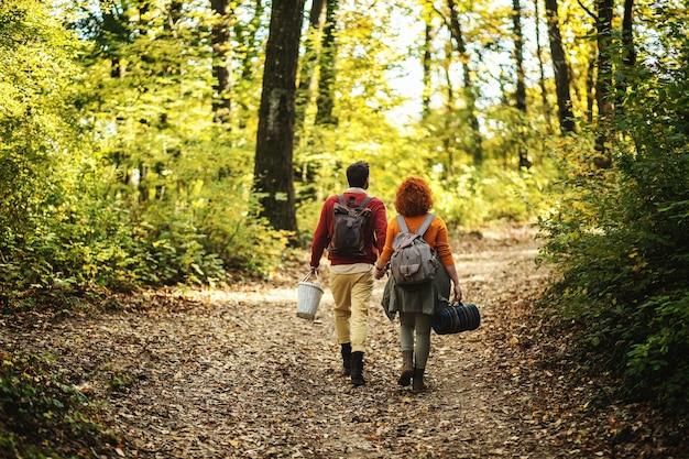 Вид сзади молодой счастливой пары в любви, держась за руки и гуляя на природе в прекрасный осенний день