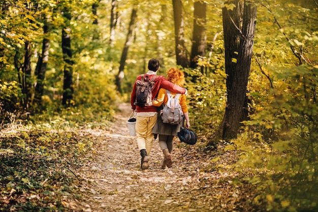 아름 다운가 날에 포옹 하 고 자연 속에서 걷는 사랑에 젊은 행복 한 커플의 후면 볼 수 있습니다. 피크닉 장비를 들고 커플입니다.