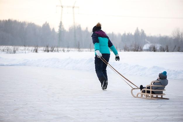 雪の降る冬の湖で一緒にそり滑りの若い幸せな母と小さな男の子の息子の背面図