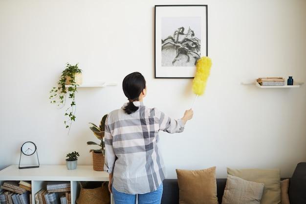 방에서 집안일을하는 동안 브러시로 먼지를 닦는 젊은 가정부의 후면보기