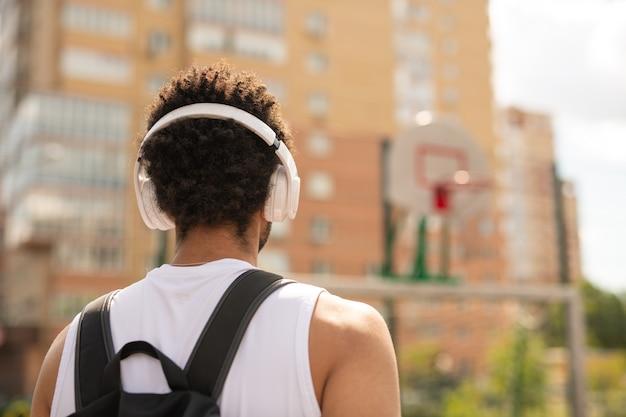 ヘッドフォンと都市環境の遊び場に立っているバックパックの若い異文化スポーツマンの背面図