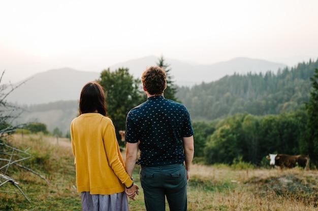 Вид сзади молодой влюбленной пары, взявшись за руки и наслаждаясь красивыми пейзажами на долину, горы и леса. летом. корова в горах. гора на заднем плане. карпаты, украина.
