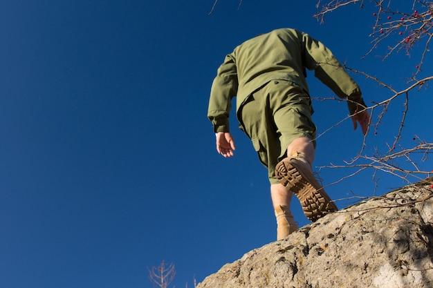 青い空を背景に古い岩に登る若い男性スカウトの背面図。