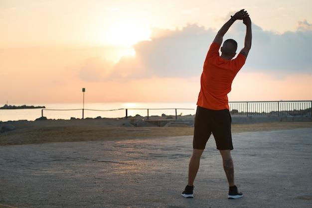 Вид сзади молодого человека, выполняющего упражнения на боковом изгибе