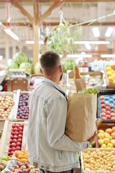紙袋を保持し、ファーマーズマーケットでジューシーな果物を選ぶライトデニムジャケットの若い男の背面図