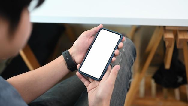 彼のワークスペースに足を組んで座って、携帯電話を使用して若い男の背面図