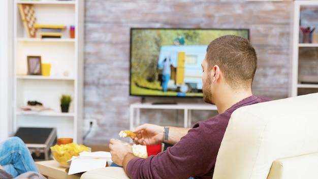 Вид сзади молодого человека, сидящего на удобном стуле, едят жареную курицу со своей девушкой перед телевизором.