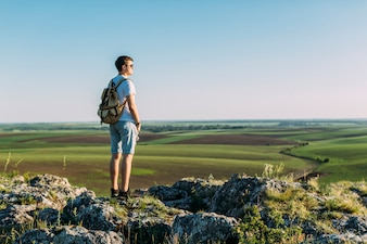 Rear view of young man standing on top of rock looking at green landscape