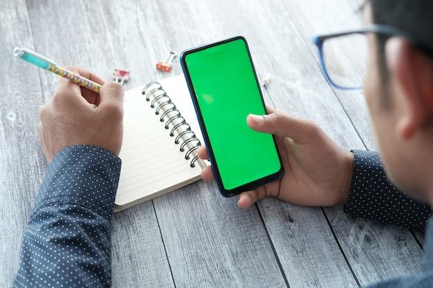 Вид сзади молодого человека с помощью смартфона и записи в блокноте