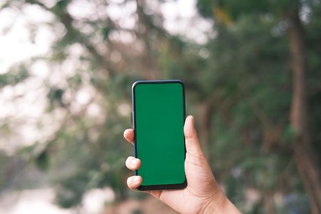 Вид сзади молодого человека, использующего смартфон на открытом воздухе