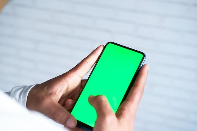 Вид сзади молодого человека, использующего смартфон в помещении